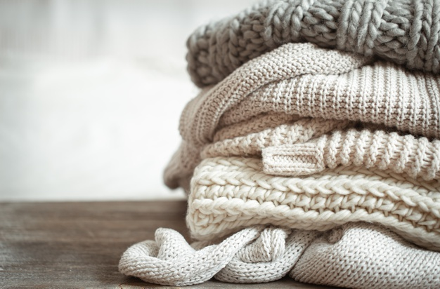 close-up-neatly-folded-knitted-items-pastel-color_169016-7137