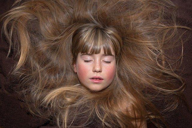 dívka obklopena vlasy