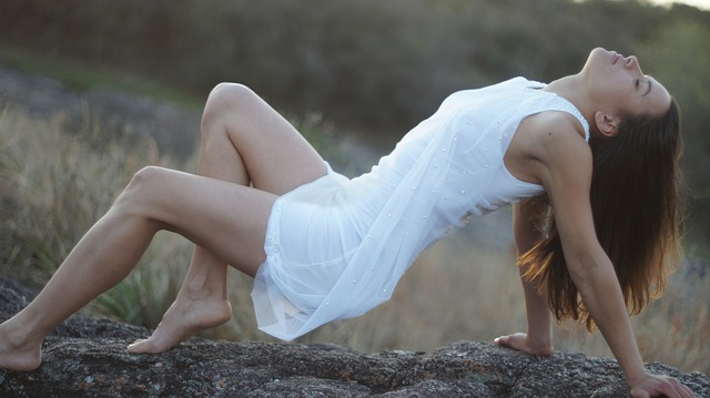 dívka na kameni v bílých šatech