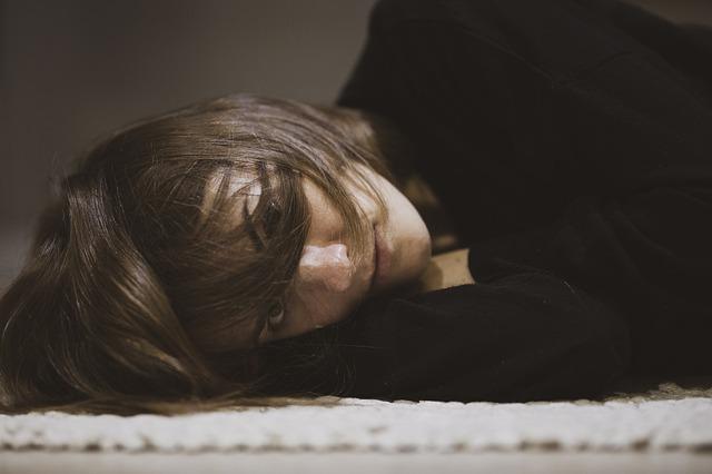 Žena s ofinou cez tvár leží na posteli.jpg