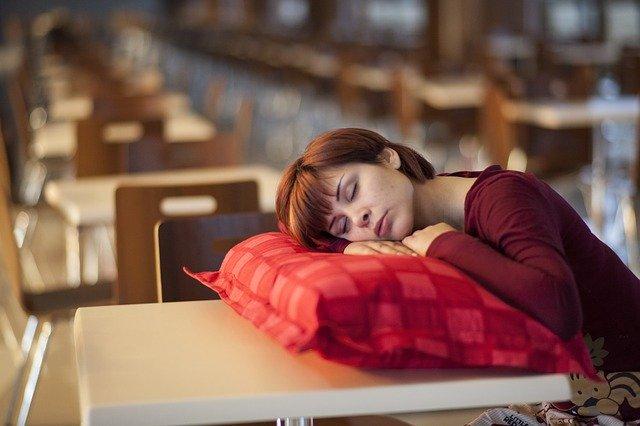Žena spí na červenom vankúši položenom na drevenej lavici.jpg