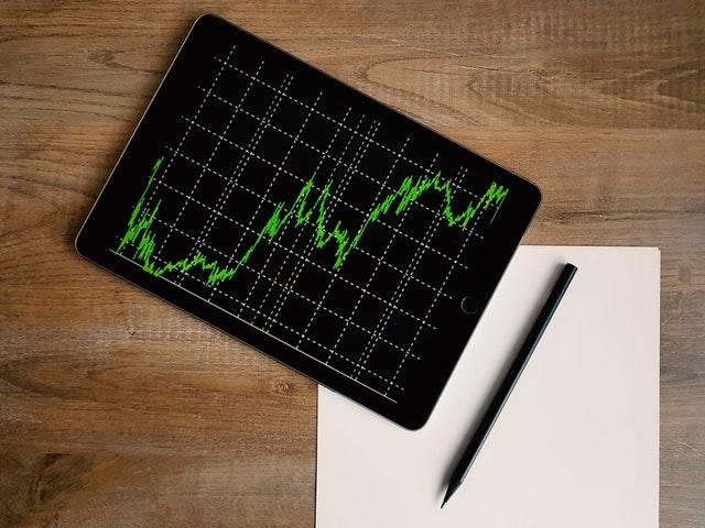 Tablet s grafom, papier a ceruzka na hnedom stole